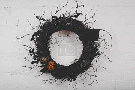 Photo pour Vue rapprochée de couronne d'Halloween fantasmagorique décorative accrochée au mur de briques blanches - image libre de droit