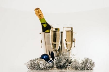 Photo for Bottle of champagne in bucket and wineglasses isolated on grey - Royalty Free Image
