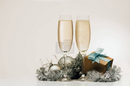 Photo for Wrapped gift, glasses of champagne and christmas decorations - Royalty Free Image