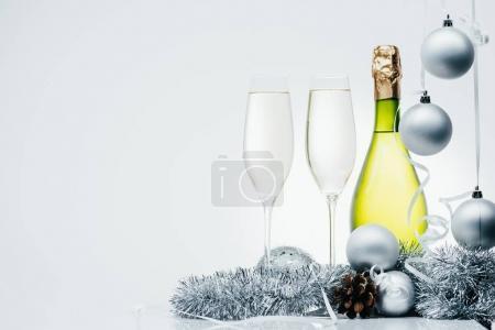 Photo pour Bouteille de champagne, verres à vin et Noël décorations isolé sur fond gris - image libre de droit