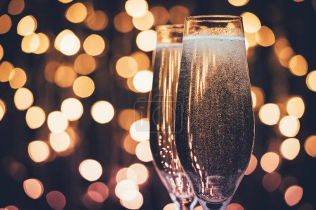Photo for Close up view of glasses of champagne with bubbles against festive lights - Royalty Free Image