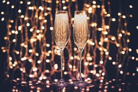 Photo for Selective focus of glasses full of champagne against christmas lights - Royalty Free Image