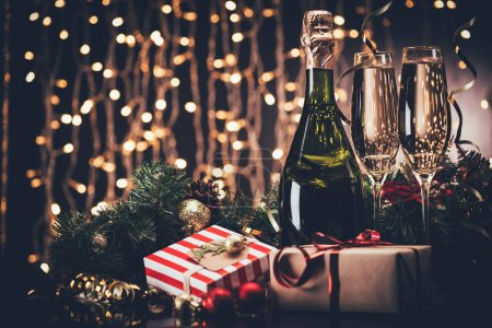 Photo for Selective focus of glasses and bottle of champagne, christmas decorations and presents against festive lights - Royalty Free Image