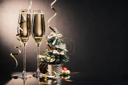 Photo for Glasses of champagne, ribbons, decorations and small christmas tree - Royalty Free Image