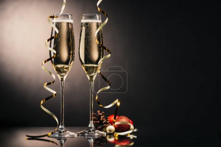 Photo for Glasses of champagne, ribbons and christmas decorations with pine cone - Royalty Free Image
