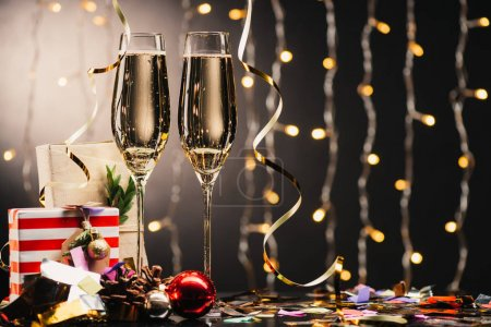 Photo for Selective focus of glasses of champagne, christmas presents and confetti against festive lights - Royalty Free Image