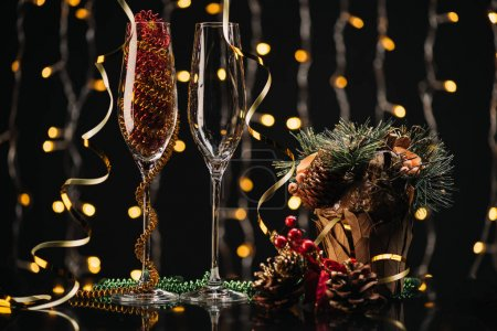 Photo for Selective focus of empty wineglasses and christmas decorations against festive lights - Royalty Free Image