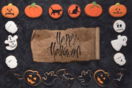 Photo for Top view of composition of halloween cookies and aged paper on black marble table - Royalty Free Image