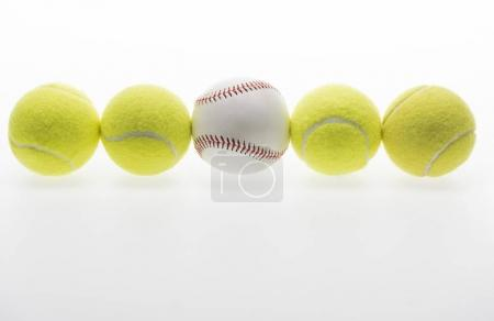 Photo for Closeup shot of tennis balls and one baseball ball isolated on white - Royalty Free Image