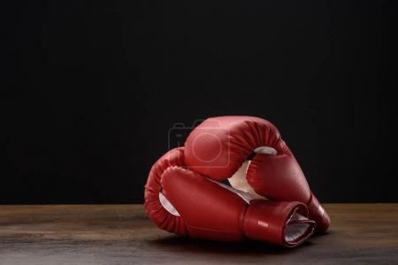 Photo pour Gros plan de gants de boxe rouges placés sur une surface en bois sombre - image libre de droit