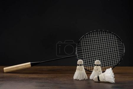 Photo pour Gros plan de raquette de badminton et trois navettes placées sur une surface en bois - image libre de droit