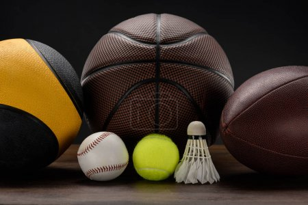 Photo for Closeup shot of various sports balls and shuttlecock on wooden surface - Royalty Free Image