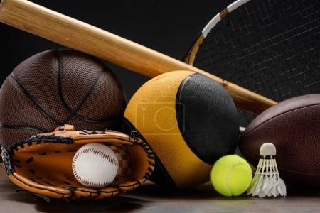 Photo pour Gros coup de divers équipements de sport, boules, batte de baseball et volant sur la surface en bois - image libre de droit