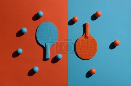 Foto de Vista superior tiro de composición con raquetas de ping pong y pelotas en dos superficie de tonos - Imagen libre de derechos