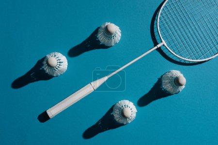 Photo pour Vue de dessus et raquette de badminton et des navettes placées sur la surface bleue - image libre de droit