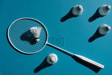 Photo pour Raquette de badminton et navettes placées sur une surface bleue - image libre de droit