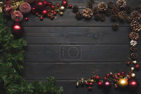 Photo for Top view of arranged shiny christmas balls, pine cones and branches on wooden surface - Royalty Free Image
