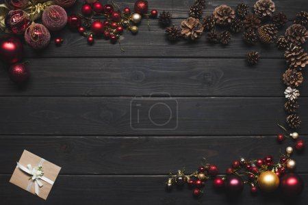 Photo for Top view of arranged shiny christmas balls, pine cones and gift card on wooden surface - Royalty Free Image