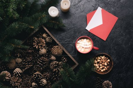 Photo for Top view of arrangement of pine cones in wooden box, candles, nuts, envelope and cup of cacao with marshmallow on black tabletop - Royalty Free Image