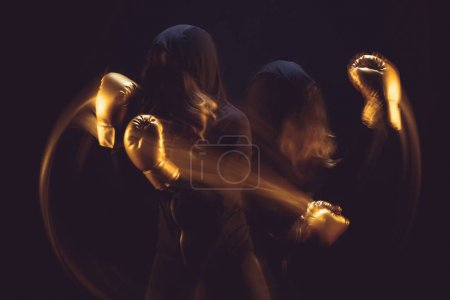 Photo for Motion shot of woman in black hoodie and boxing gloves exercising isolated on black - Royalty Free Image