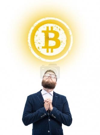 praying businessman with bitcoin