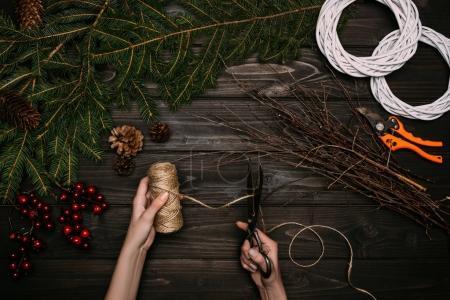 Photo pour Recadrée vue des mains de fleuriste faire des couronnes de Noël avec des branches et pommes de pin sur le dessus de table en bois - image libre de droit
