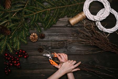 Photo pour Vue de dessus des mains de fleuriste en guirlande de Noël avec des branches et sécateur sur table en bois - image libre de droit