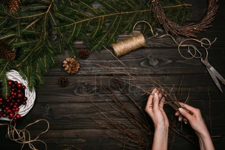 Photo pour Vue de dessus des mains de fleuriste en guirlande de Noël avec des branches sur une table en bois - image libre de droit