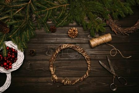 Photo for Top view of creation of Christmas wreath with fir and twine on wooden tabletop - Royalty Free Image