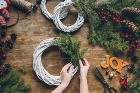 Photo for Top view of florist hands making Christmas wreath with fir branches and word Joy on wooden tabletop - Royalty Free Image