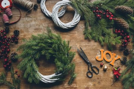 Photo for Top view of creation of Christmas wreaths with fir branches and pine cones on wooden table with word Joy and scissors - Royalty Free Image