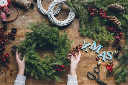 Photo for Top view of florist hands making Christmas wreath with fir branches and decorative berries, with word Xmas on wooden tabletop - Royalty Free Image