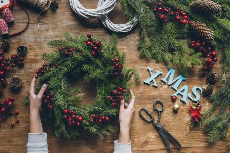 Photo for Top view of female hands holding Christmas wreath with fir branches and decorative berries, with word Xmas on wooden tabletop - Royalty Free Image