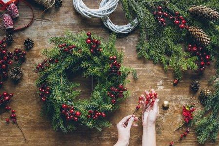 Photo pour Vue de dessus des mains de fleuriste faisant la couronne de Noël avec des branches de sapin et des baies décoratives sur le dessus de table en bois - image libre de droit