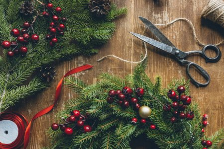 Photo for Close up view of Christmas wreath with fir, decorative berries and pine cones on wooden tabletop with scissors - Royalty Free Image