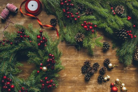Photo for Top view of Christmas wreath with fir, decorative berries and pine cones on wooden tabletop - Royalty Free Image