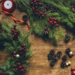 Top view of Christmas wreath with fir, decorative berries and pine cones on wooden tabletop