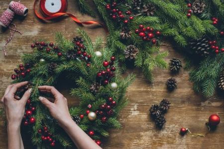 Foto de Vista superior de las manos de Floreria hacer guirnalda de la Navidad en tablero de madera - Imagen libre de derechos