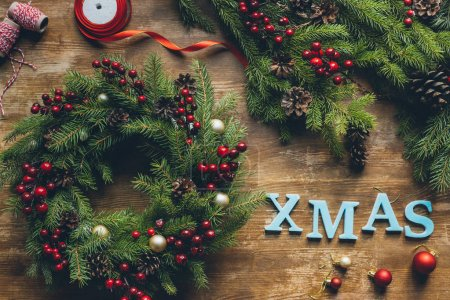 Photo for Top view of Christmas wreath with fir, decorative berries and pine cones on wooden tabletop with Xmas sign - Royalty Free Image