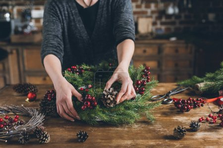 Photo for Cropped view of florist making Christmas wreath of fir branches, decorative berries and pine cones at workplace - Royalty Free Image