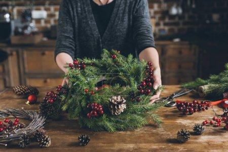Foto de Vista recortada de Floreria sosteniendo la guirnalda de la Navidad de ramas de abeto, bayas decorativas y conos de pino en el lugar de trabajo - Imagen libre de derechos