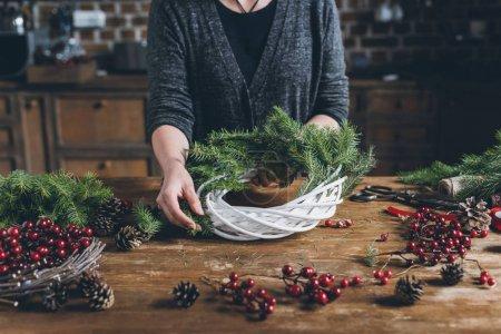 Foto de Recortar vista de Floreria hacer Navidad guirnalda de ramas de abeto, bayas decorativas y conos de pino en el lugar de trabajo - Imagen libre de derechos