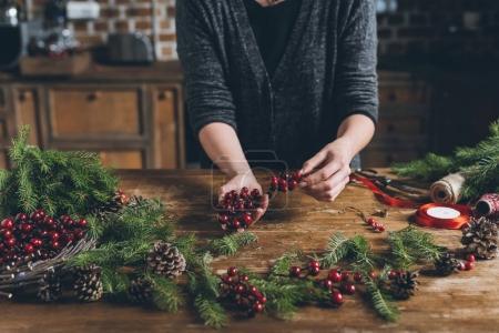 Foto de Recortar vista de Floreria hacer decoraciones de Navidad de ramas de abeto, bayas decorativas y conos de pino en el lugar de trabajo - Imagen libre de derechos
