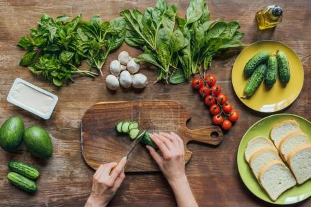 Photo for Top view of female hands cutting fresh cucumber while cooking breakfast - Royalty Free Image