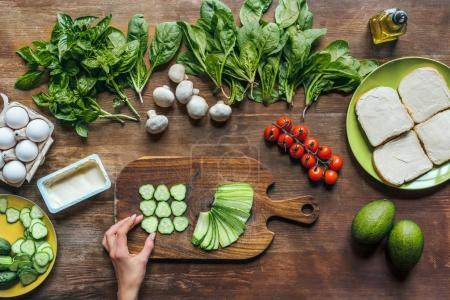Photo for Top view of female hand, fresh cut cucumber pieces and other ingredients for healthy breakfast - Royalty Free Image