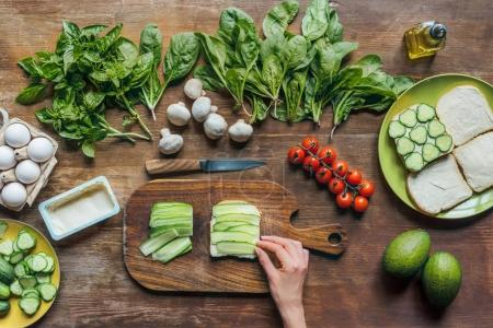 Photo for Partial view of woman making toasts with various ingredients for breakfast - Royalty Free Image