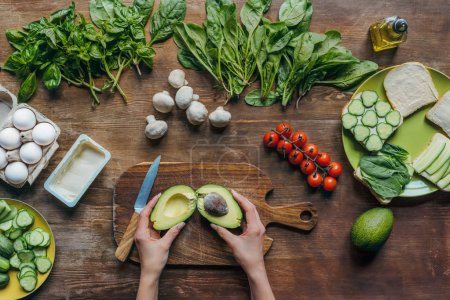 Photo for Partial view of female hands preparing avocado while cooking homemade healthy breakfast - Royalty Free Image