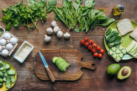 Photo for Flat lay with fresh avocado on cutting board and various ingredients for cooking healthy breakfast on wooden tabletop - Royalty Free Image