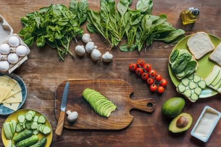 Foto de Endecha plana con aguacate fresco sobre tablero de corte y varios ingredientes para cocinar un desayuno saludable en tablero de madera - Imagen libre de derechos