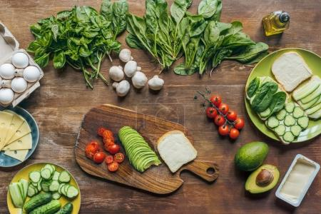 Photo for Flat lay with various arranged healthy vegetables, mushrooms and raw chicken eggs for cooking breakfast on wooden tabletop - Royalty Free Image